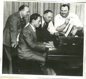 "Photograph of George Gershwin at the piano. Left to right: Ferde Grofé, Samuel ""Roxy"" Rothafel, and Paul Whiteman"