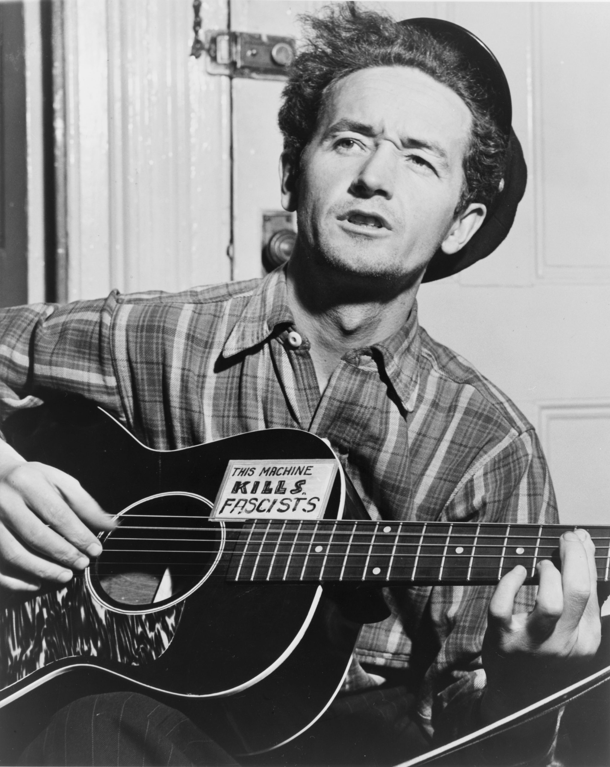 "Woody Guthrie in 1943; the sticker on his guitar says ""This Machine Kills Fascists"""