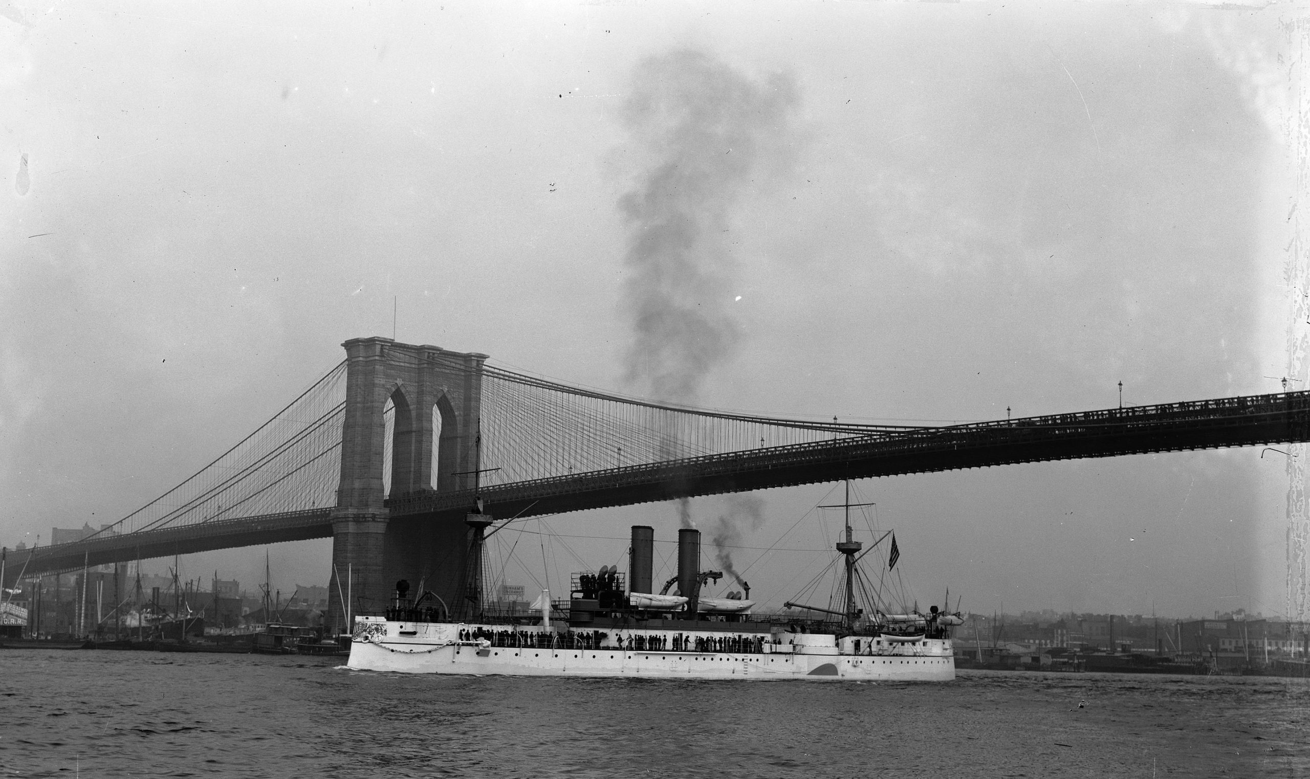 The USS Maine in better times, passing under the Brooklyn Bridge